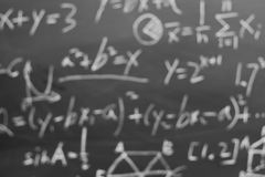 Maths formulas on chalkboard bokeh. Blurred maths formulas written by white chalk on the blackboard background Stock Image