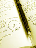 Maths reference book and pen
