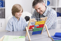 Maths? It's easy!. Shot of a men and his son using an abacus to study Royalty Free Stock Photos