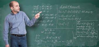 Maths teacher. Friendly maths teacher by the blackboard stock images