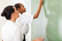 Maths teacher teaching. Primary school maths teacher teaching student in classroom Royalty Free Stock Photo
