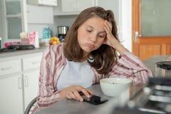 Matin, adolescente à l'aide du smartphone dans la cuisine photographie stock libre de droits