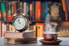 Matin avec le thé et les livres chauds images stock