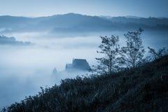 Matin brumeux mystérieux au-dessus de village de Biertan, la Transylvanie, Roumanie Photos stock
