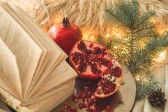 Matin confortable d'hiver à la maison Livre et grenade dans une composition en hiver, arbres de Noël, cônes Oreillers et guirland images stock