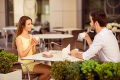 Matin délicieux Deux amants mignons s'asseyent en café léger sur le su Image libre de droits