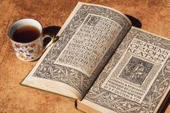 Matin d'un rat de bibliothèque avec le livre du 18ème siècle des poèmes de John Keats et de la tasse de conception florale de caf Image stock