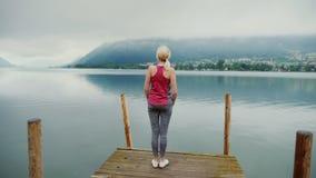 Matin dans les Alpes près du lac de montagne Une femme fait une rupture sur un pilier en bois clips vidéos
