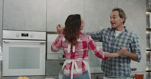 Matin dans les couples mûrs romantiques de cuisine dacing tout en faisant le petit déjeuner pendant le matin clips vidéos