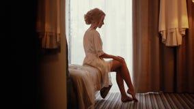 Matin de la jeune mariée La jeune mariée près de la fenêtre banque de vidéos