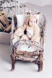 Matin de Noël Petite fille dans des cerfs communs de salopette se reposant dans un toboggan photos stock