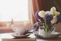 Matin de ressort à la maison avec la tasse de café, de livre et de fleurs sur la table blanche Images stock