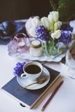 Matin de ressort à la maison avec la tasse de café, de livre et de fleurs sur la table blanche Image stock
