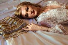 Matin du ` s de jeune mariée - portrait de jeune femme blonde dans la lingerie blanche avec sa robe de mariage Image libre de droits