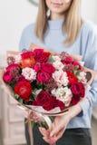 Matin ensoleillé de source Jeune femme heureuse tenant un beau bouquet de luxe des fleurs mélangées le travail du fleuriste à photographie stock