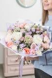 Matin ensoleillé de source Jeune femme heureuse tenant un beau bouquet de luxe des fleurs mélangées le travail du fleuriste à image stock
