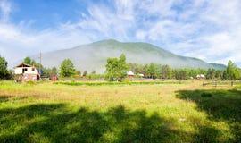 Matin ensoleillé tôt à côté de la forêt et des maisons en bois Le brouillard se lève au-dessus de l'herbe Beau ciel avec de desso Photos stock