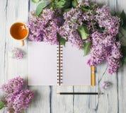 Matin sur la table avec la note, la tasse de thé et les fleurs Photo stock