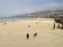 Matin typique à la plage de la Californie comme promenade de personnes sur le sable Photographie stock libre de droits