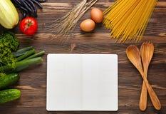Matingrediens med receptboken på träbakgrund Royaltyfri Fotografi