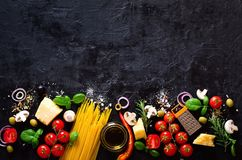 Matingredienser för italiensk pasta, spagetti på den svarta stenen kritiserar bakgrund kopieringsutrymme av din text royaltyfri bild