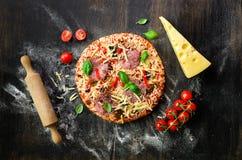 Matingredienser för italiensk pizza, körsbärsröda tomater, mjöl, ost, basilika, kavel, kryddor på mörk bakgrund överkant royaltyfri fotografi