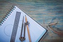 Matita controllata della bussola di disegno del righello del quaderno su di legno d'annata Immagine Stock