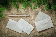 Matita della carta per buste del ramoscello dell'albero di abete sul fondo di insaccamento fotografia stock libera da diritti