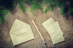Matita della carta per buste del ramoscello dell'albero di abete sul fondo di insaccamento fotografie stock