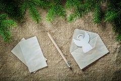 Matita di angelo della carta per buste del ramoscello dell'albero di abete sulla superficie di insaccamento immagini stock libere da diritti