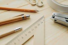 Matita di legno, penna, triangolo, clip più briefpapier, hefter sullo scrittorio nella luce del giorno Tavola dell'ufficio Fotografia Stock