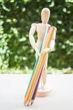 Matita di trasporto di colore del manichino di legno sulla tavola di lavoro dell'artista Fotografia Stock