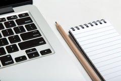 Matita e blocco note accanto alla tastiera del computer portatile Fotografia Stock