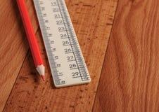 Matita e righello rossi su un fondo di legno Rifornimenti di banco immagine stock