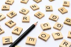 Matita nera e lettere sparse di alfabeto sui blocchi di legno su fondo bianco immagini stock