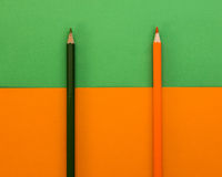 Matita nera ed arancio su un fondo verde ed arancio Fotografie Stock