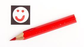 Matita rossa che sceglie il giusto umore, come o a differenza di/avversione Fotografia Stock