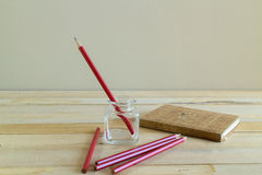 Matita rossa con il taccuino sulla tavola di legno Fotografie Stock