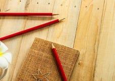 Matita rossa con il taccuino sulla tavola di legno Fotografia Stock