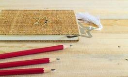 Matita rossa con il taccuino sulla tavola di legno Fotografia Stock Libera da Diritti