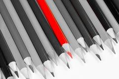 Matita rossa con le altre matite in bianco e nero contro un contesto bianco fotografia stock