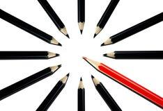 Matita rossa fra le matite nere Fotografia Stock