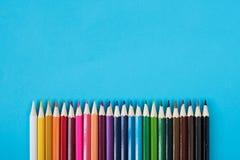 Matite colorate isolate su fondo blu Immagini Stock Libere da Diritti