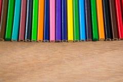 Matite colorate sistemate in una fila Immagine Stock