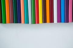 Matite colorate sistemate in una fila Fotografie Stock