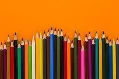 Matite colorate su un fondo arancio Immagini Stock Libere da Diritti