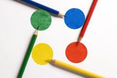 Matite colorate sui dischi colorati sistemati come strade trasversali Fotografia Stock Libera da Diritti