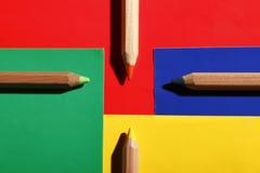 Matite colorate sulle carte colorate sistemate come strade trasversali Fotografia Stock Libera da Diritti