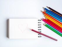 Matite colorate variopinte e un cuscinetto di disegno con un cuore immagini stock