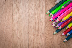 Matite di colore della pila su fondo di legno fotografia stock libera da diritti